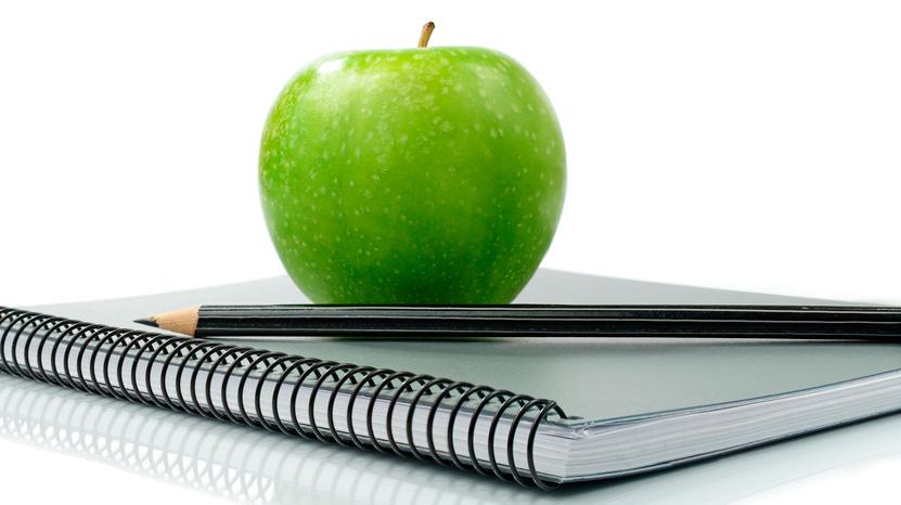 Fotografía de un libro, una manzana y un bolígrafo